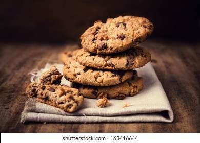 Chocolate cookies on white linen napkin on wooden table. Chocolate chip cookies shot on coffee colored cloth, closeup.