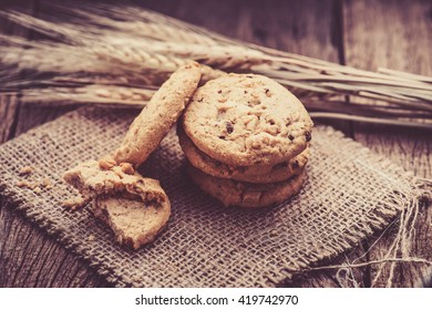 Chocolate cookies on white linen napkin on wooden table. Chocolate chip cookies shot on sack