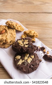 Chocolate cookies on white napkin on wooden table.