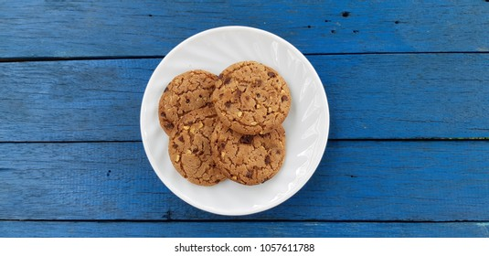 Chocolate cookies placed on a blue wooden table.