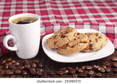 Chocolate cookies in plate and cup of hot coffee on wooden table covert tablecloth