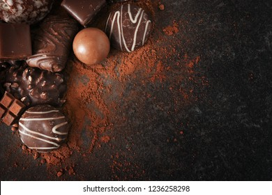 chocolate cookies and pralines for christmas and advent on a dark slate plate  with large copy space, high angle view from above