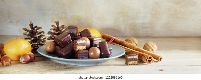 Chocolate cookies and sweets for Christmas and Advent on a rustic wooden table, panoramic format with copy space, selected focus, narrow depth of field