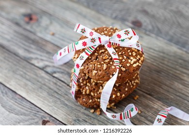 Chocolate cookies tied with Christmas ribbon. Oat cookies with nuts, sesame and chocolate on wooden background.