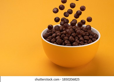 Chocolate Corn balls falling in bowl over yellow background with copy space, healthy breakfast cereal