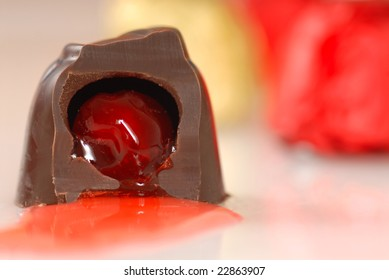 Chocolate covered cherry that has been bitten into so its juice flows out
