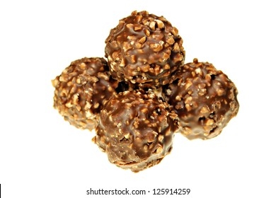 Chocolate covered crushed hazelnuts isolated on white