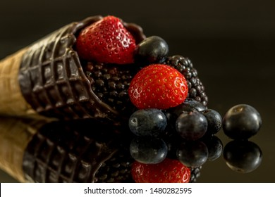 Chocolate covered ice cone with Strawberries, blueberries and blackberries