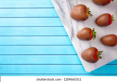 Chocolate Covered Strawberries on a Blue Wooden Table
