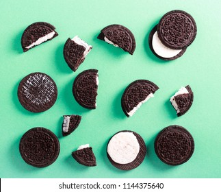 Chocolate cream filling sandwich cookies over green background, top view