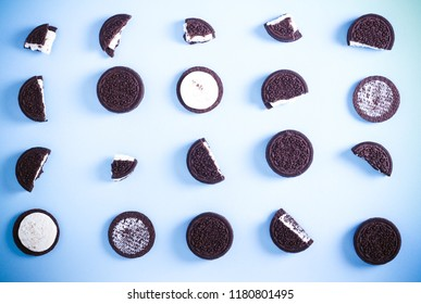 Chocolate cream filling sandwich cookies over blue background