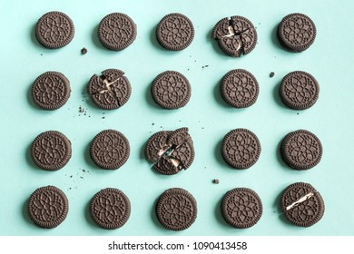 Chocolate and cream sandwich cookies on blue pastel background, top view.
