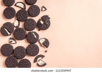 Chocolate and cream sandwich cookies on pink pastel background, top view, copy space.