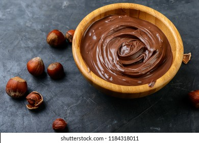 chocolate cream in a wooden bowl, chocolate pieces  and hazelnuts on dark background