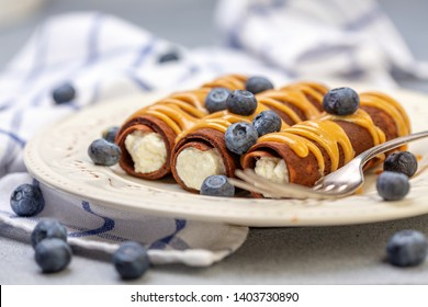 Chocolate crepes with cottage cheese, caramel sauce and berries for breakfast, selective focus.