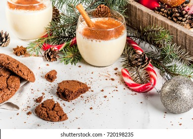 Chocolate Crinkle cookies for Christmas, with eggnog cocktail, candy cane, Christmas tree and holiday decoration, on white marble table, copy space
