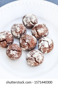 Chocolate crinkle cookies on a white plate, Cracked chocolate biscuits, Chocolate cookies in powdered sugar with cracks