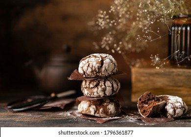 Chocolate crinkle cookies with powdered sugar icing. Homemade cracked chocolate brownie biscuits on brown wooden rustic table. Selective focus, copy space.