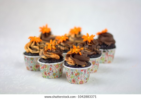 Chocolate Cup cakes with ganache cream and orange color flower on top. selective focus