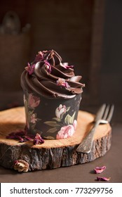 Chocolate cupcake decorated with rose petals in a rustic wooden background. Shot in natural light.