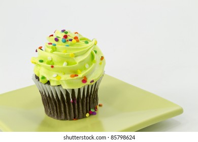Chocolate cupcake with green frosting and multicolored sprinkles sits on square, green plate, a single, tempting symbol of fresh, baked, and festive baked goods.