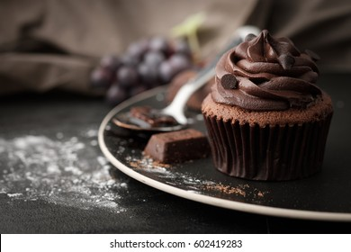 Chocolate cupcake with icing and chocolate bar in Dark lighting, AF point selection.