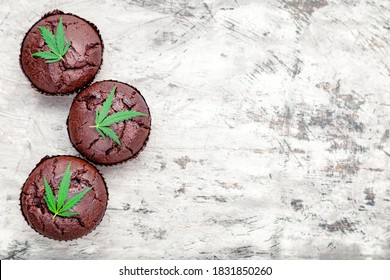 Chocolate cupcake muffins with cannabis leaves weed cbd. Medical marijuana hemp drugs in food dessert. Cooking baking weed muffins with marijuana on gray concrete background. Copy space. Top view.