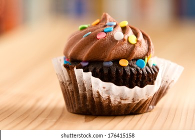 Chocolate Cupcake - This is a shot of a delicious cupcake covered in sprinkles sitting on a wooden table top. Shot with a shallow depth of field.