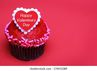 Chocolate cupcake with Valentines heart on the top, over red background with space for the text.