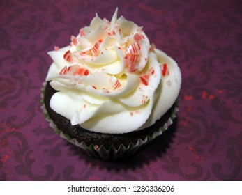 Chocolate cupcake with white frosting, garnished with candy cane pieces