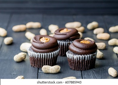 Chocolate cupcakes filled with peanut butter and topped with chocolate mousse. Homemade bakery. Rustic background.