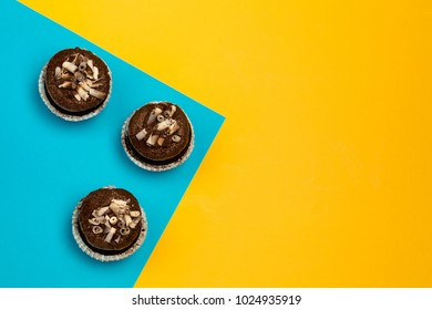 chocolate cupcakes on a color yellow-blue background decorated with chocolate shaving