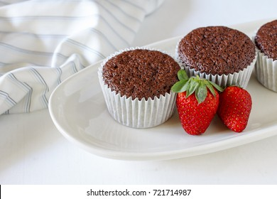 Chocolate cupcakes on white plate and fresh strawberry.