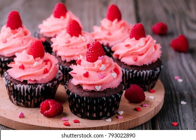 Chocolate cupcakes with pink cream, sugar hearts and fresh raspberries for St. Valentine's Day