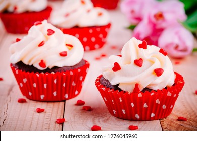 Chocolate cupcakes with vanilla cream and red sugar hearts for St. Valentine's Day