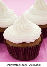 Chocolate cupcakes with whipped cream. Shallow dof.