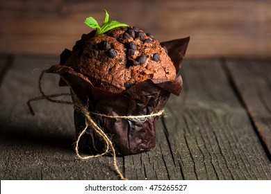 chocolate dark muffin with a leaf of mint on a wooden table with cinnamon, anise, chocolate