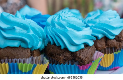 Chocolate dark muffins with blue cream on top, homemade bakery, close up, selective focus