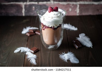 Chocolate dessert in glasses with raspberries. Chocolate mousse or pudding in portion glasses with fresh berries, rustic style. A white feathers and chokolate on wooden table.