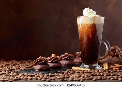 Chocolate dessert with hazelnut and coffee with cream on a wooden table.Coffee beans and cinnamon sticks are scattered on the table.