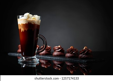 Chocolate dessert with hazelnut and coffee with cream on a black reflective background. Copy space for your text.