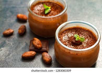Chocolate dessert panna cotta in glass jars with raw cocoa beans