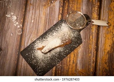Chocolate dessert with powdered sugar on wooden table