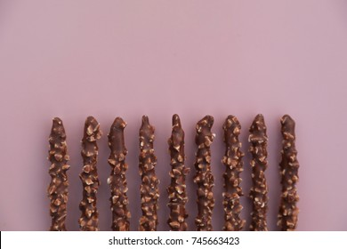 Chocolate dipped biscuit sticks above a pink background