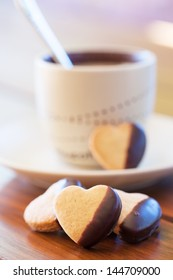 Chocolate dipped heart shaped cookies and cup of coffee on wooden table