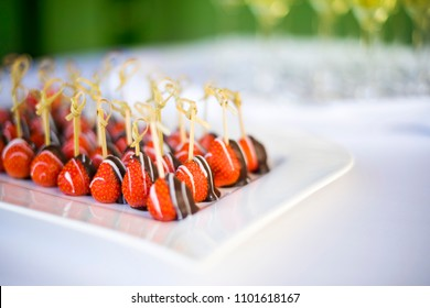 Chocolate dipped strawberries on a plate at a wedding table. Catering setup