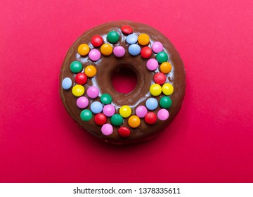 Chocolate donut decorated with colorful smarties isolated on red color background, top close up view