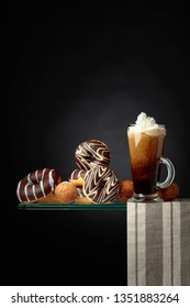 Chocolate donuts and coffee cocktail with cream on a black background. Copy space for your text.