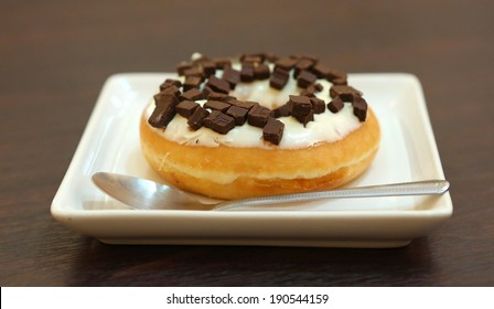 Chocolate donuts in plate with spoon against wood background