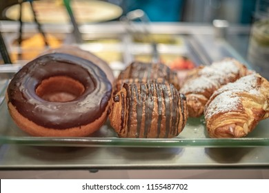 A chocolate doughnut, chocolate filled croissant and almond croissant pastry for sale.